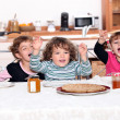 Portrait of children eating at table — Stock Photo
