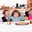 Portrait of children eating at table - Stock Photo