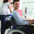 Man in wheelchair at work — Stock Photo #7608781