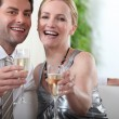Couple sitting with arms stretched towards camera holding champagne glasses - Stock Photo