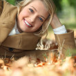 Stock Photo: Young womlying amidst autumnal foliage in woods