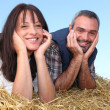 Farmer and wife laying in hay — Stock Photo