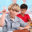 Boy raising his hand in class — Stock Photo