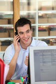 Male office worker speaking to customer on the telephone — Stock Photo