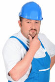 Construction worker in blue overalls and hardhat — Stockfoto