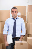 Man in storage depot surrounded by boxes — Stock Photo