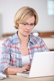 Woman using a laptop computer at home — Stock Photo