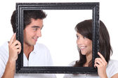 Young couple behind photo frame — Stock Photo