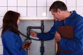 A mature plumber teaching to a female apprentice — Stock Photo