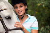 Young woman caressing her horse — Stock Photo