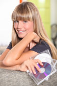 Blonde teenager behind a couch and holding cd cases — Stockfoto
