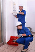 Two electricians working, one is setting an electricity meter — Stock Photo