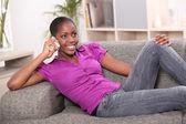 Une femme afro-américaine sur le téléphone posé sur un canapé — Photo