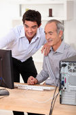 Younger and older men looking at a computer — Stock Photo