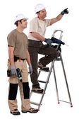 Two laborers with drills chatting — Stock Photo