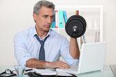 Zakenman oefeningen maken in zijn kantoor — Stockfoto