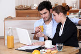 Woman going over a work presentation with her boyfriend during breakfast — Stock Photo