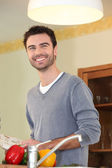 Smiling chap looking at a cookbook — Stock Photo