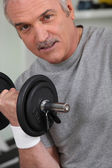 A mature man doing fitness with dumbbell — Stock Photo