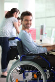 Man in wheelchair at work — Stock Photo