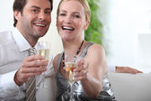 Couple sitting with arms stretched towards camera holding champagne glasses — Stock Photo