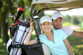 Couple in golf cart — Stock Photo