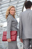 Woman carrying briefcase with colleague — Stock Photo