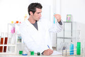 Young man studying the contents of a test tube and making notes accordingly — Stock Photo