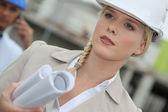 Arquiteto feminino em um capacete de segurança com planos — Foto Stock