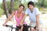 Couple cycling through a coastal pine forest — Stok fotoğraf