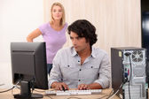 Male on his computer with his wife in the back. — Stock Photo