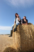 Couple sitting on bail of hay — Stock Photo