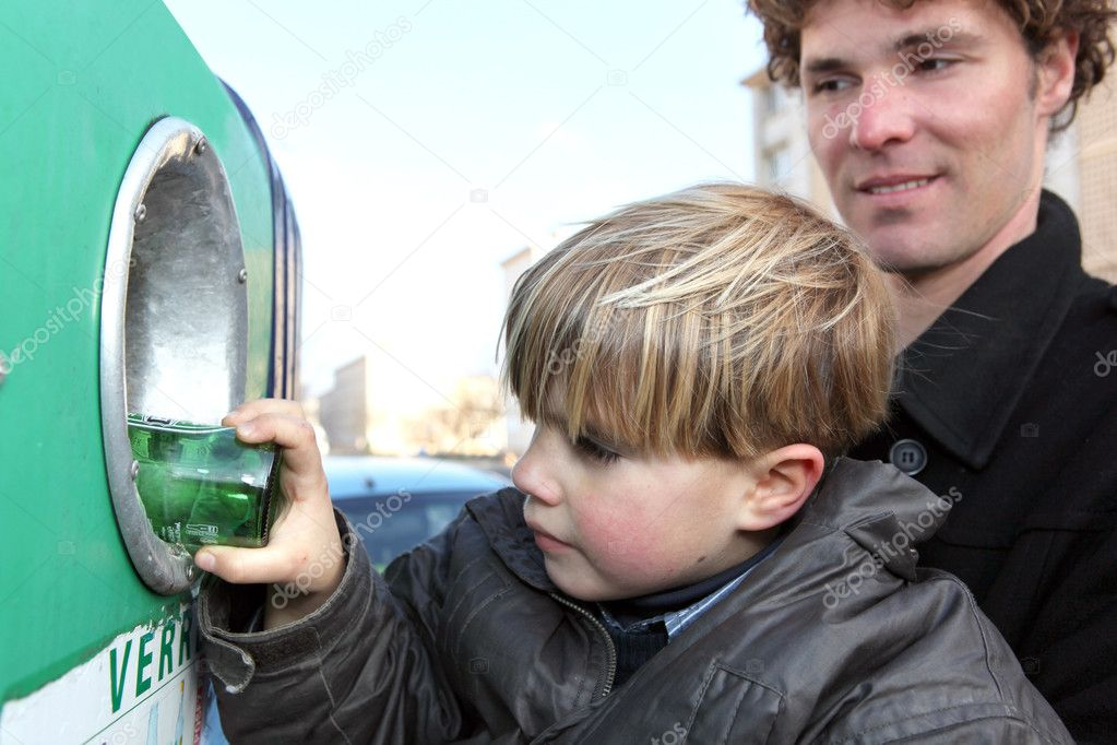 Little boy putting a glass bottle into a recycling bin — Stock Photo #7607349
