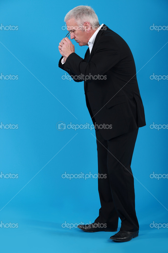 Businessman putting his eyeglasses on to look for an object  Stock Photo #7608573
