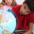 Stock Photo: Children at school with a globe