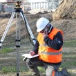 Foto Stock: Land surveyor writing in his notebook while talking on phone