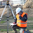 ストック写真: Land surveyor writing in his notebook while talking on phone