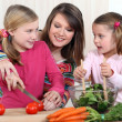 Mother chopping vegetables with two daughters — Stockfoto #7611909
