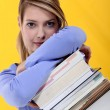 Stock Photo: Womleaning on stack of books