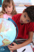 Children at school with a globe — Stock Photo
