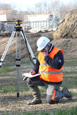 A land surveyor writing in his notebook while talking on the phone — Foto de Stock