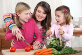 Mother chopping vegetables with two daughters — Stock Photo