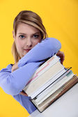Woman leaning on a stack of books — Stock Photo