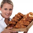 Blonde woman holding a platter of croissants - Stock Photo