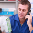 Plumbers merchant on the phone with a part in hand - Foto de Stock
