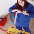 Female plumber with grey plastic pipe and tools - Foto de Stock