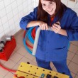 Female plumber with grey plastic pipe and tools - Lizenzfreies Foto