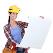 Stock Photo: Tradeswomexamining blueprint