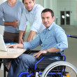 Man in a wheelchair pictured with colleagues — Stock Photo
