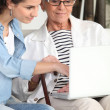Young woman helping an elderly lady navigate the internet — Stock Photo #7623317